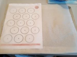 Plaque avec gabarit sous le papier sulfurisé pour des macarons réguliers.